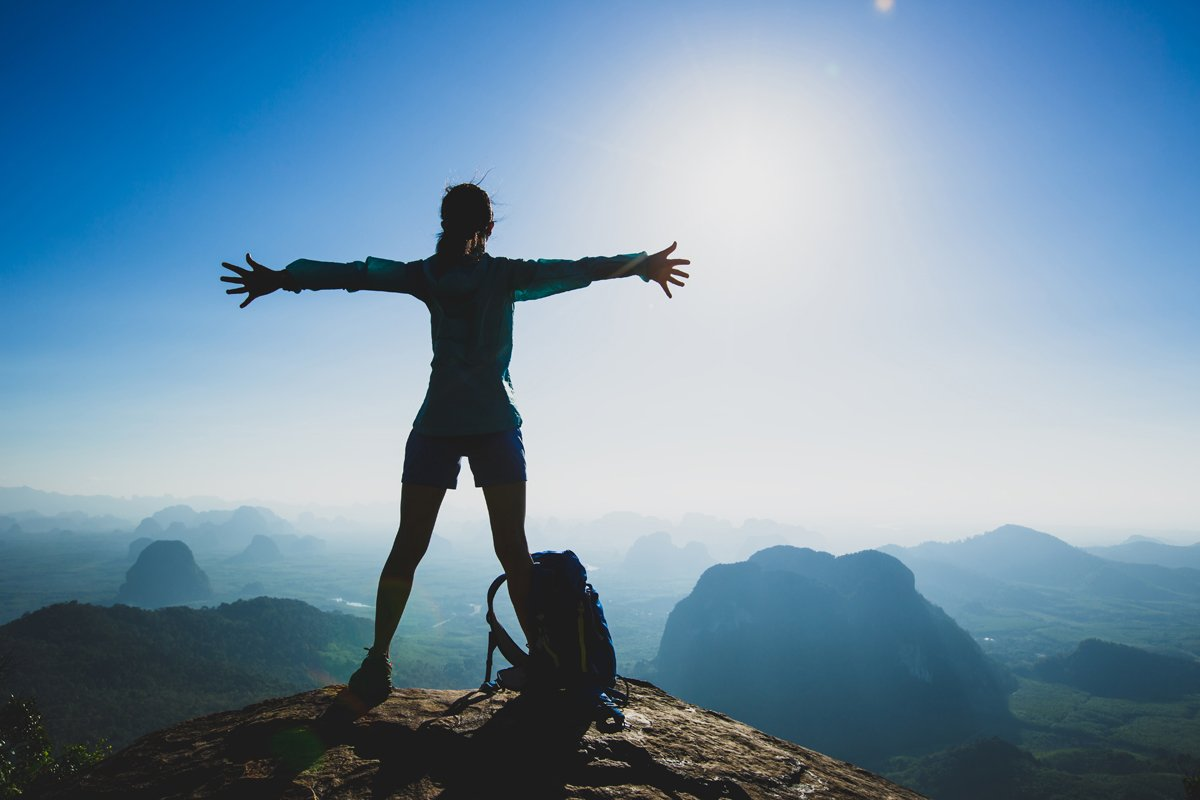 woman standing on mountain top, arms outstreached looking up at sky