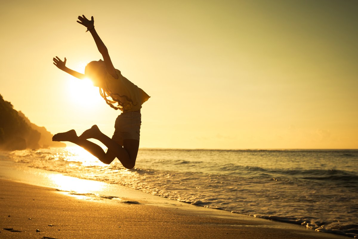 woman jumping for joy at beach sunset