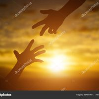 Silhouette of giving a help hand, hope and support each other over sunset background. Concept of helping hands and develop a friendship.