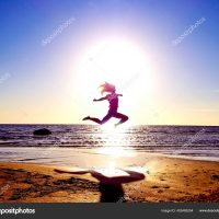 silhouette of a girl on the background of the sun disk in a jump on the sandy seashore in an interesting pose